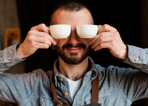 Speelse man poseren met koffiekopjes