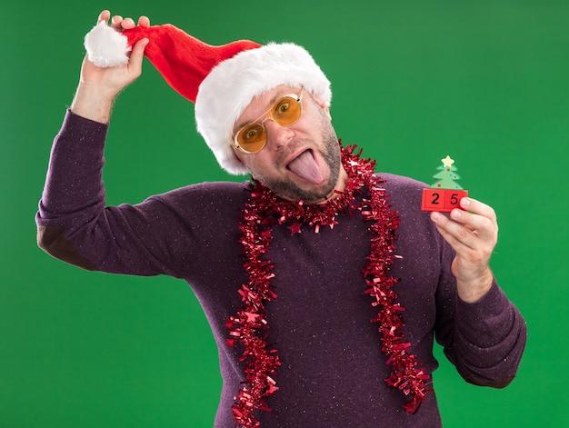 Speelse man van middelbare leeftijd met kerstmuts en klatergoud slinger om nek met glazen kerstboom speelgoed met datum te houden