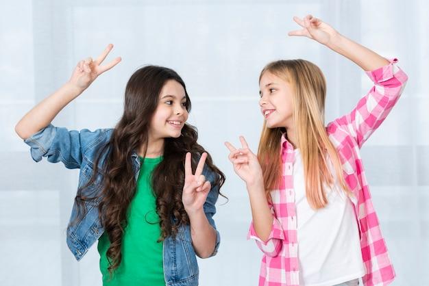 Speelse meisjes die vredesteken tonen