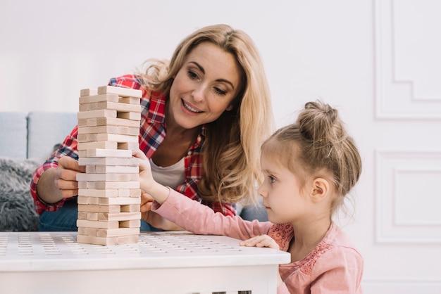Speelse moeder en dochter in de woonkamer