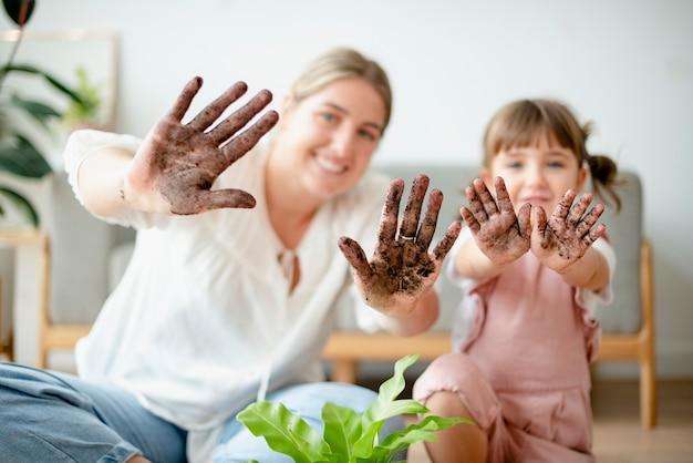 Speelse moeder en kind potplant in huis