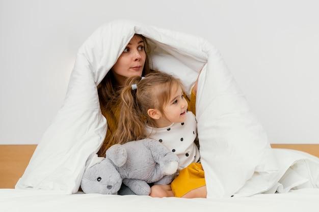 Speelse moeder en kind verstopt onder een deken