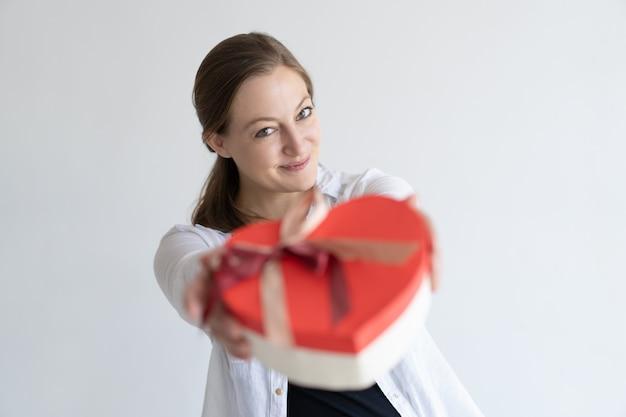 Speelse mooie jonge vrouw die hart gevormde geschenkdoos geeft