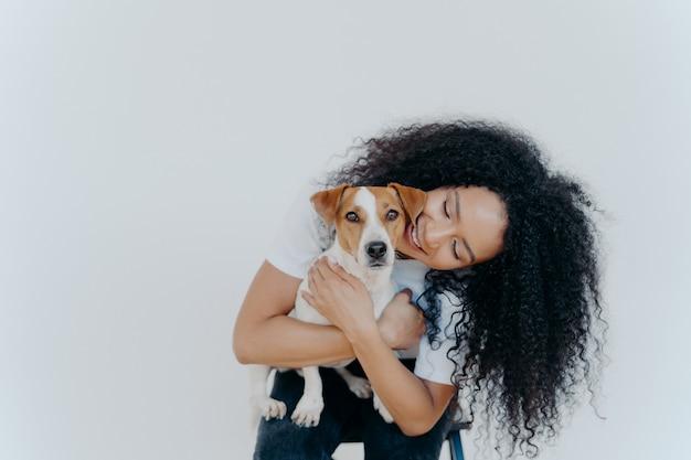 Speelse mooie vrouw met afro-kapsel, glimlacht blij, houdt huisdier vast