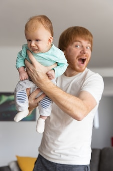 Speelse opgewonden nieuwe vader die zoete baby houdt