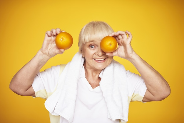 Speelse oude dame houdt sinaasappels vitamine c concept.