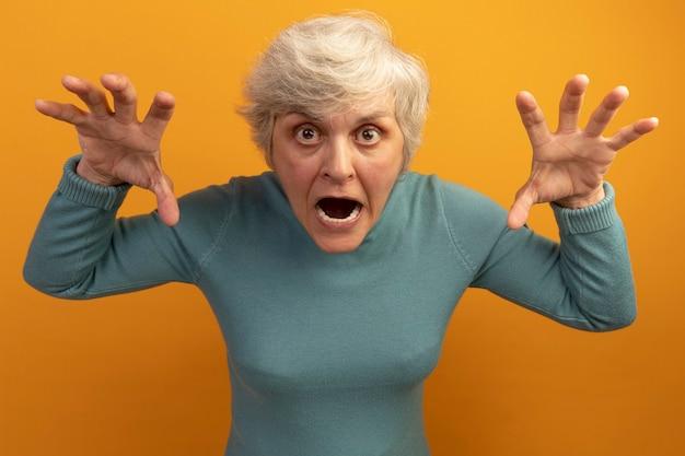 Speelse oude vrouw met blauwe coltrui die tijgergebrul en pootgebaar doet
