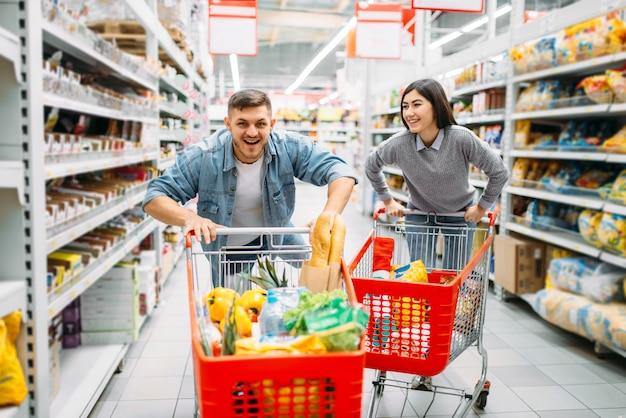 Speelse paar rijden op karren in de supermarkt, familie winkelen. klanten in de winkel, kopers in de markt