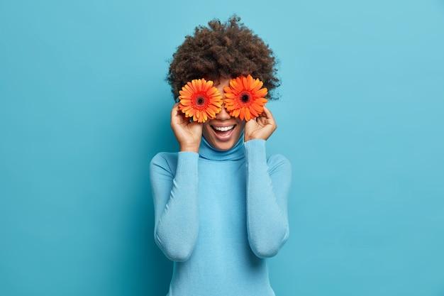 Speelse positieve afro-amerikaanse vrouw bedekt ogen met twee oranje gerbera's, geniet van de lentetijd, verse bloemen, heeft plezier, nonchalant gekleed,