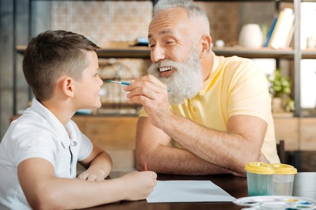 Speelse sfeer. gelukkig oudere man nadert een penseel met een groene waterverf erop en wil terwijl hij glimlacht een stip op de neus van zijn kleinzoon zetten