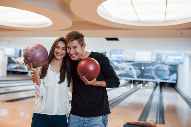 Speelse sfeer. jonge, vrolijke vrienden vermaken zich in het weekend in de bowlingclub