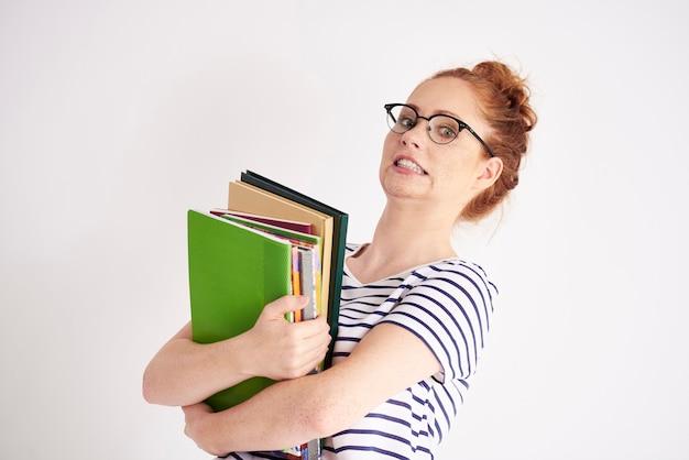 Speelse student die een stapel zware boeken vasthoudt