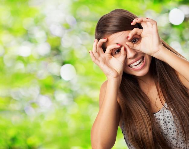 Speelse tiener toont bril gebaar