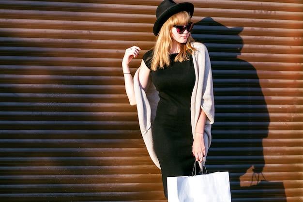 Speelse verlegen vrouw verbergen shopping pack, timide lachen. leuke vrouw die lacht gelukkig door handen. zwarte hoed, grijze jas, zwarte jurk, herfstkleren. warme winterstijl