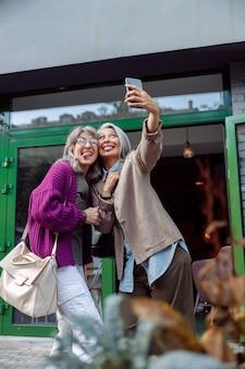 Speelse volwassen vrouw met aziatische vriend neemt selfie met tongen op moderne stadsstraat