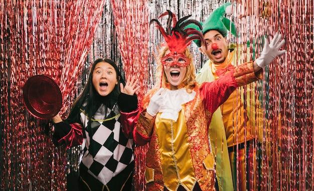 Speelse vrienden met kostuums op feestje