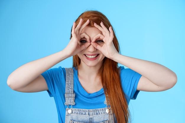 Speelse vrolijke roodharige europese vrouw, lang natuurrood kapsel, oke vingerbril laten zien, door ok tekens kijken, breed lachend grappige grimas, staan blauwe achtergrond zorgeloos geniet van de zomer