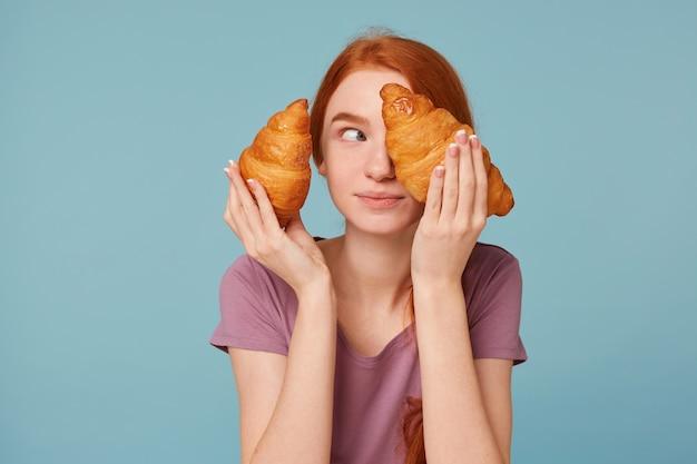 Speelse vrolijke roodharige vrouw met twee croissants in haar handen, kijkt weg, dekt sluit haar oog met een croissant,