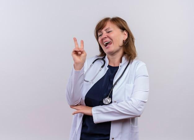 Speelse vrouw arts van middelbare leeftijd die medische mantel en stethoscoop draagt die vredesteken doet en tong toont op geïsoleerde witte muur met exemplaarruimte