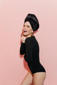 Speelse vrouw in tulband die naar voren kijkt