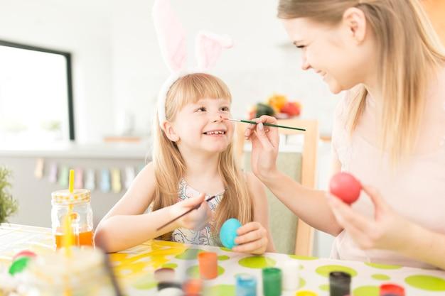 Speelse vrouw met dochter die voor pasen voorbereidingen treft