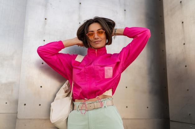 Speelse vrouw met plezier in neon roze jasje over grijze metalen stedelijke muur