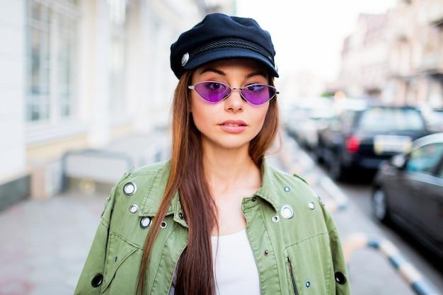 Speelse vrouw poseren buiten. trendy paarse retro bril, zwarte pet