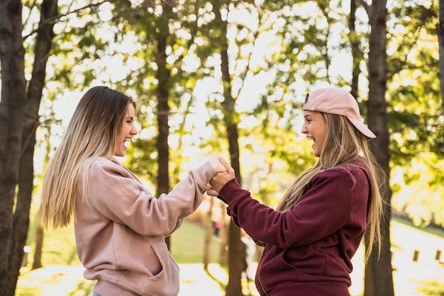Speelse vrouwen houden elkaars handen vast