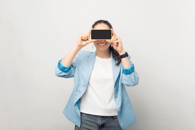 Speelse zakenvrouw bedekt haar ogen met het scherm van de telefoon die ze vasthoudt.
