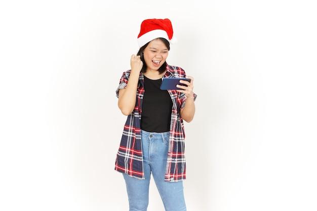 Speelspel op smartphone van mooie aziatische vrouw met rood geruit hemd en kerstmuts