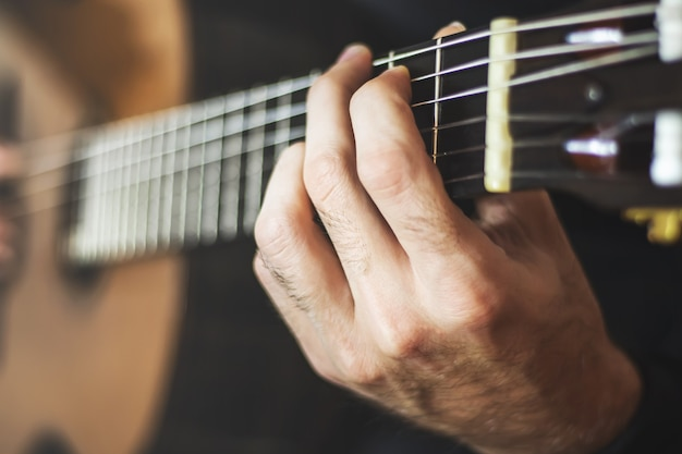 Speelt akoestische gitaar close-up