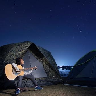 Speelt de gitaar van het meisje bij tent gloeit onder de sterren van een nachthemel
