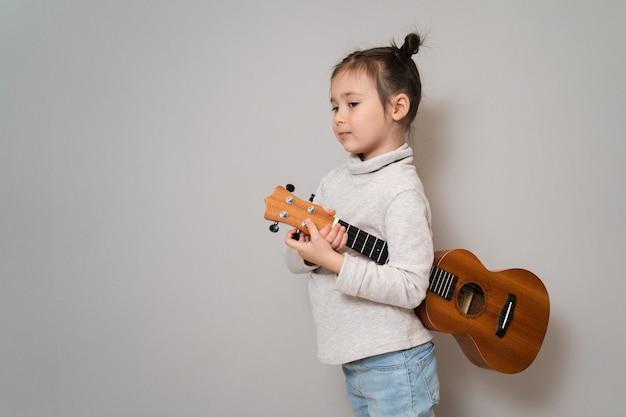 Speelt ukelele en zingt ontwikkeling in de vroege kinderjaren het meisje heeft muzikaal talent mooi meisje dat zingt en gitaar speelt