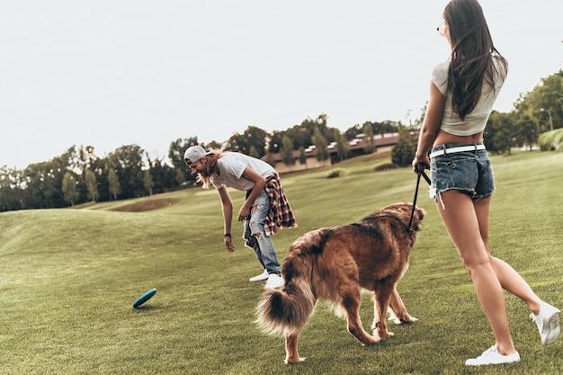 Speeltijd! volledige lengte van mooi jong stel dat plastic schijf gooit terwijl ze buiten met hun hond spelen