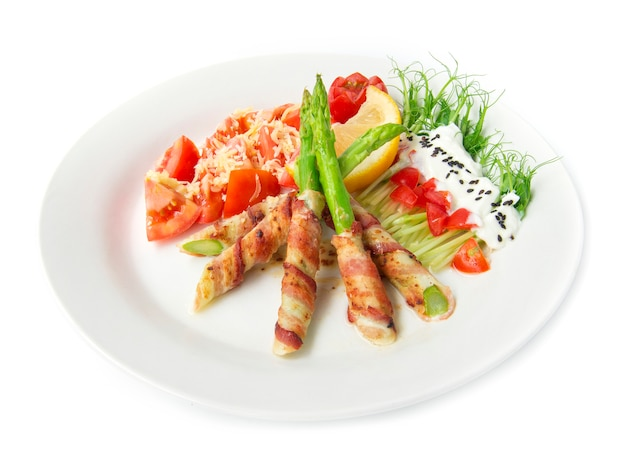 Spek gewikkeld asperges gegrild met erwtenspruiten rol salade op griekse yoghurt bestrooi zwarte sasemi en tomatensalade op cheddar kaas versieren met citroen en gesneden tomaat stijl zijaanzicht