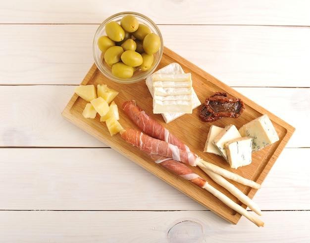 Spek op broodstengels, kaas, gedroogde tomaten, olijven op een houten bord