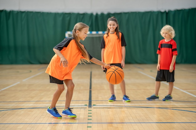 Spel. een meisje speelt met een bal en kijkt betrokken terwijl vrienden wachten
