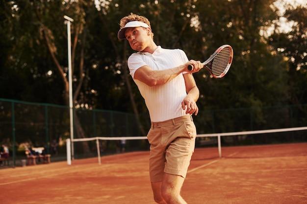 Spel in actie. jonge tennisser in sportieve kleding is buiten op het veld.