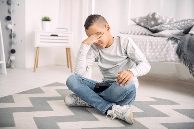 Spel is over. triest afro-amerikaanse jongen die zijn ogen bedekt terwijl hij op de vloer zit