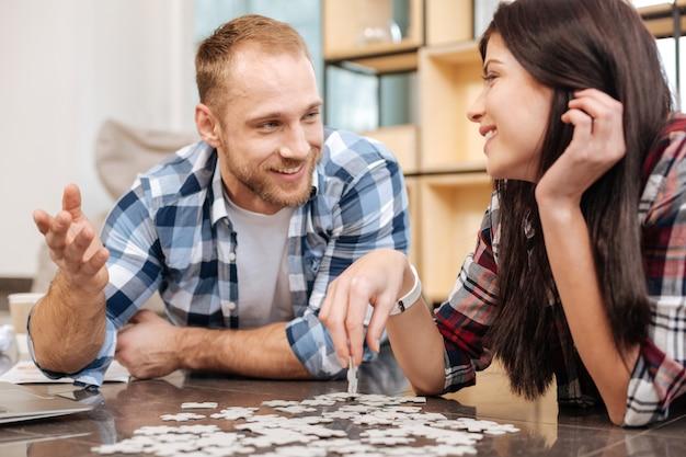 Spel ontwikkelen. vrolijke aantrekkelijke gelukkige vrouw die een puzzelstukje vasthoudt en lacht terwijl ze een geweldige tijd heeft met haar vriend