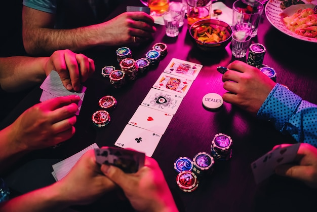 Spel van pokerkaarten en chips op de tafel met de handen van de spelers