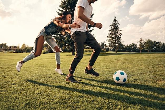 Spel wordt heter. aantrekkelijke jonge vrouw en moderne man in vrijetijdskleding rennen tijdens het voetballen buiten