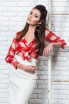 Speld omhoog als stijlportret van een aardige jonge brunette over een witte bakstenen muur