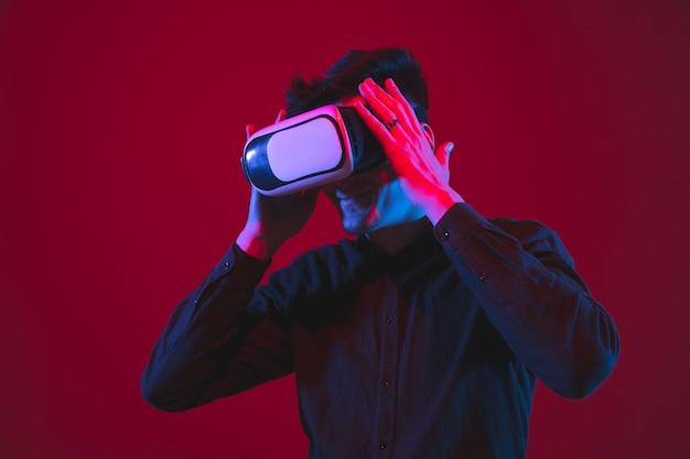 Spelen droeg een vr-headset. portret van een blanke jongeman geïsoleerd op rode muur in neonlicht. mooi modelletje. concept van menselijke emoties, gezichtsuitdrukking, jeugd, apparaten.