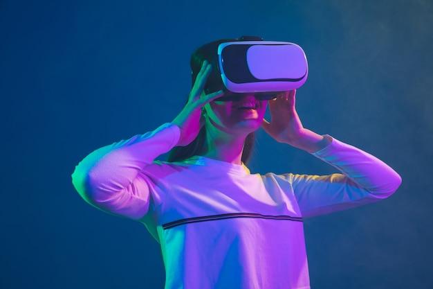 Spelen in actie. portret van de blanke jonge vrouw geïsoleerd op blauwe studio achtergrond in neon licht. mooi vrouwelijk model. concept van menselijke emoties, gezichtsuitdrukking, verkoop, advertentie, jeugdcultuur.