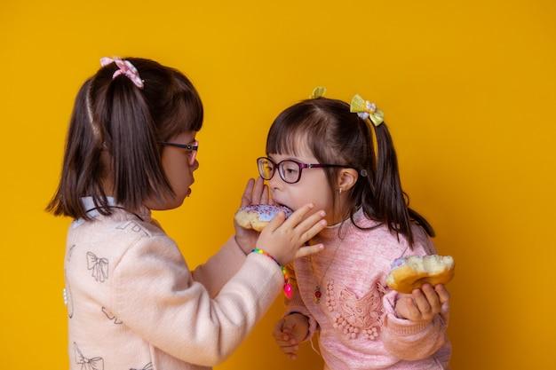 Spelen met eten. vriendelijke donkerharige dame die haar mooie zus met blauwe donut voedt terwijl ze tegen elkaar aan staan