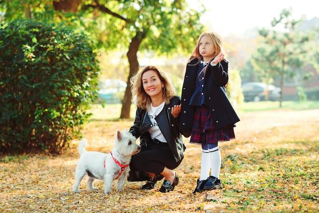 Spelen met hond in herfst park en gelukkige familie
