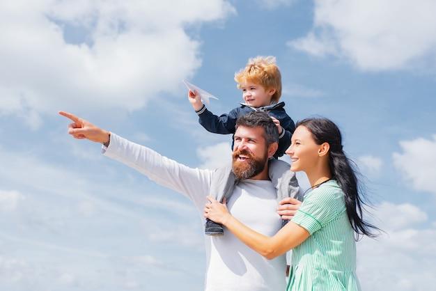 Spelen met papieren vliegtuigje buiten en gelukkige familie