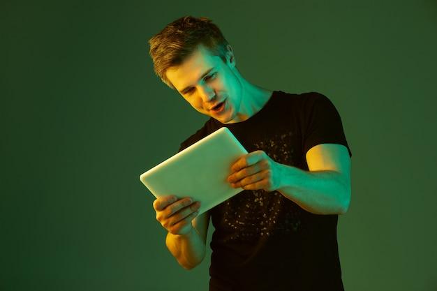 Spelen met tablet. blanke man portret geïsoleerd op groene studio achtergrond in neonlicht.
