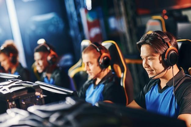 Spelen om te winnen. gelukkige aziatische mannelijke cybersport-gamer die een koptelefoon draagt die deelneemt aan esport-toernooien en glimlacht, online videogames speelt. wazig teamleden op de achtergrond Premium Foto